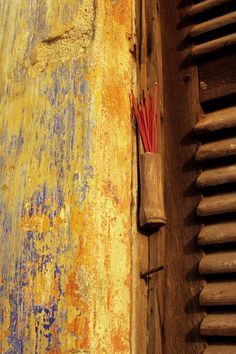 Incense sticks in a bamboo holder on a weathered wall, Hoi An, Viet Nam | © Rick Piper