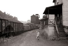 Coal miner's child taking home kerosene for lamps. Company houses and a coal tipple are in the background in Scotts Run, near Morgantown.  (September, 1938. Marion Post Wolcott photo.)