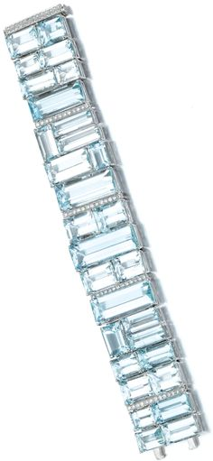 Aquamarine and diamond bracelet.  Designed as a wide band, set with variously sized step-cut aquamarines in a geometric pattern, highlighted with lines of brilliant-cut diamonds, length approximately 190mm. Sotheby's.