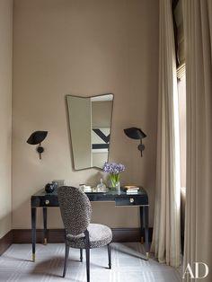 Serge Mouille sconces flank a 1950s Italian mirror above the master bedroom's vintage De Coene Frères desk
