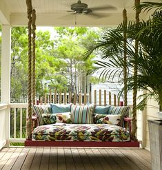 A daybed porch swing with tropical style fabric, hanging on rope.