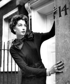 Model is wearing sweater in black jersey with a satin pussycat bow and striped silk skirt, one of the creations of Maxime de la Falaise at her show in London, photo by John Chillingworth, 1954