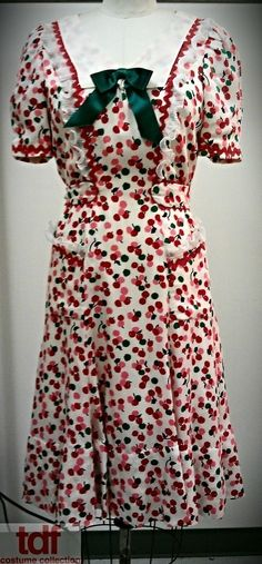 Let's start off with a light subject and say that this dress falls into the category: Spring. It's so cute and the pattern is of little pink and red cherries. It's hard to see in the pattern but there is also some adorable trim along the sleeves and pockets. The perfect outfit for a spring outing. #TDFCC #KeepingUpWithTheCostumes #1940s