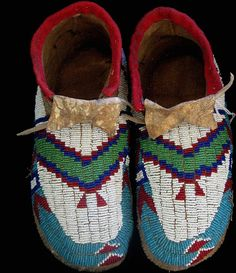 1890's Lakota men's Moccasins with buffalo soles. These turn of the century moccasins of brain tan deer and buffalo par fleche soles are edged in red trade wool and feature wonderful sinew sewn beadwork. In wonderful condition and with beautiful old colors of cobalt, Sioux green, clear wine red and chalk white beads