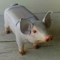I won this pig we call Wilbur on eBay years ago. He is wood and leather and hand carved. He is the size of a real piglet and is actually a footstool. BUT we just keep him around because he's so darn cute! Louise Glass