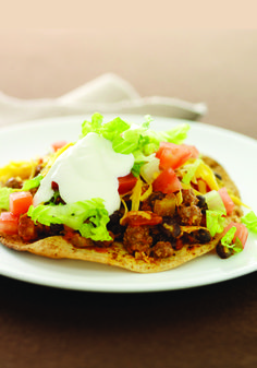 Cheesy Beef Tostadas – Spicy beef. Hearty beans. Shredded cheese. Lettuce, tomato, and a dollop of sour cream atop a crispy tortilla. All that—in one Healthy Living, Mexican-inspired, dinnertime recipe.