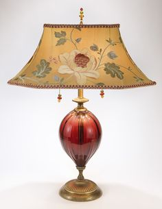 Frida table lamp by Kinzig Design has a red, hand blown glass piece on the stem, and a rectangular, dupioni silk shade, with floral design. Colors: mustard, salmon, red, gold, green. Solid brass and c