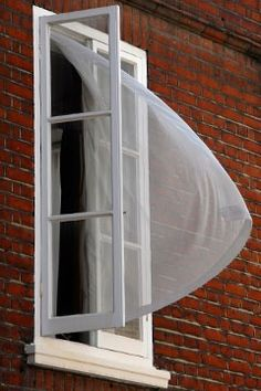 curtain blowing out of a window in London breeze