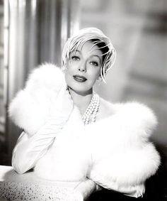 Loretta Young wearing a white fur and feather hat...