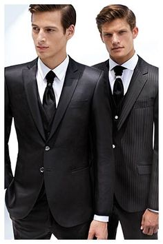 Black tailored suit with a white shirt and coloured tie.