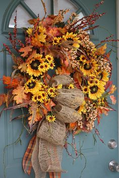 Gorgeous fall wreath with Sunflowers and Burlap ribbon. Lovely! Pin, save and Click thru to see the candle lantern sunflower topper with pumpkins!