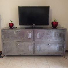 Repurposed school lockers. Clear rust guard over bare metal outside, inside painted machinery grey. One shelf cut out to fit DVD player/ Wii. Whole cut out of back to thread electrical cords through. Four lockable castors used . Industrial look. Great for a garage or man cave. Fun project.
