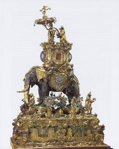 Musical Automaton, 1768-1772, London, England, chased bronze, gilt-bronze, paste, mother of pearl, carved oak base. The elephant is operated by 2 keys inserted in the belly of the elephant & the base. The base plays a musical tune. The triumphal Emperor riding the elephant & the 4 musicians on the base move to & fro. The paste flowers, designed to imitate diamonds, rotate & open & close. Glass roundels in the base reveal revolving snakes & stars, & architectural scenes. Waddesdon Collection