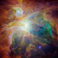 The Spitzer and Hubble Space Telescope combine to show the chaos of baby stars some 1,500 light-years away in the Orion nebula. The orange dots are infant stars. Hubble shows less embedded stars as specks of green, and foreground stars as blue spots.