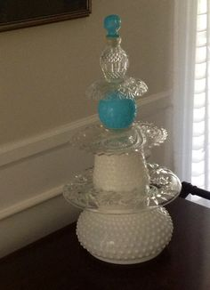 Centerpiece constructed from crystal, hobnail milk glass, and a vintage Avon bottle