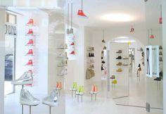 In questa immagine del negozio Ruco Line di Roma si vedono le calzature esposte su piedistalli in metallo che si ergono da terra o che pendono dai soffitti