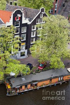 City of Amsterdam traditional Dutch style houses and a houseboat on a canal in Netherlands, view from above.