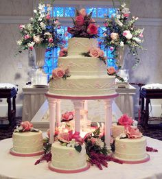 This cake is the right shape. The pink pillars should be white and the little satellite cakes are unnecessary. I like the three tiers on the top though and how the cake fully covers the cake board. Bling Wedding Cakes, Purple Wedding Cakes, Amazing Wedding Cakes, Wedding Cake Stands, Elegant Wedding Cakes, Wedding Cake Designs, Castle Wedding Cake, Elegant Cakes, Wedding Cupcakes