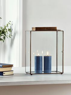Perfect for creating an ambient glow in your living space, our large rustic metal lantern has glass sides and a glass hinged door to allow the light from your candle to shine though, and a burnished brass frame. Place near a window or in an unused fireplace for maximum effect.