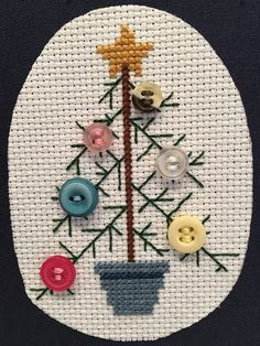 This is a vintage wood framed cross stitch Christmas tree with multi-colored button ornaments displayed on a navy blue cloth. Oatmeal 14 count aida cloth was used for the tree area. Cross Stitch Christmas Ornaments, Xmas Cross Stitch, Cross Stitch Cards, Christmas Embroidery, Christmas Cross, Cross Stitching, Cross Stitch Embroidery, Embroidery Patterns, Button Ornaments