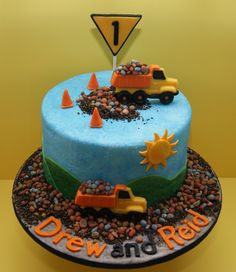 My Dumptruck Birthday Cake - This is a dump truck themed cake for twin boys. It is a vanilla cake with vanilla buttercream filling and is covered with fondant. I added some royal icing for texture in the sky. The dirt is crushed cookies. The sun, trucks, cones, rocks are modeling chocolate.