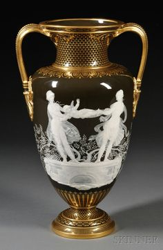 Minton Marc-Louis Solon Decorated Pate-Sur-Pate Vase, England, late 19th century, dark brown ground with gilded handles and border designs, either side white slip decorated, one with depiction of two maidens swinging a figure of Cupid, the reverse with large cherub supported with strings to arms and legs held by groups of small cherubs, inscribed signature, impressed and printed marks, ht. 16 in.