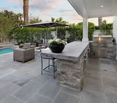 The outdoor kitchen features concrete countertop and stone. These pavers are a natural stone called Shadow Gray. Outdoor Kitchen Layout Brandon Architects, Inc Outdoor Kitchen Countertops, Outdoor Kitchen Bars, Outdoor Kitchen Design, Concrete Countertops, Patio Design, Outdoor Kitchens, Patio Kitchen, Concrete Kitchen, Theoule Sur Mer