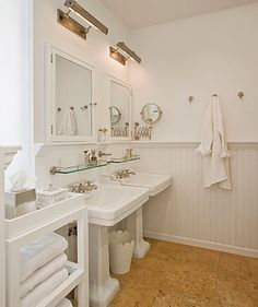 White farmhouse style bathroom with two pedestal sinks. Glass shelves, brass lights and cork flooring.