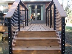 Beautiful Timbertech Earthwoods composite deck with stainless steel cable rails mounted on black steel posts. Wire Deck Railing, Stainless Steel Cable Railing, Composite Decking, Wpc Decking, Backyard Retreat, Patio, Fence Design, Exterior Design, Outdoor Living