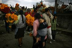 People, some carrying flowers, gather at a cemetery during Day of the Dead celebrations in San Miguel Canoa, central Mexico