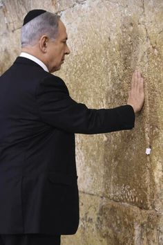 Israeli Prime Minister Benjamin Netanyahu prays at the Western Wall before boarding his flight to Washington, DC ahead of his speech before Congress on March 3, 2015.