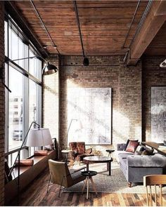 Aestate. Industrial living room with high ceilings, a brick wall, and huge windows.
