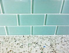 aqua glass subway tile with recycled glass counter. Notice the flecks of aqua glass in the countertop, and how the white grouting sets it all off..