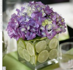 A small, square, glass vases stuffed with sliced limes and purple hydrangeas to sit at the center of the tables.