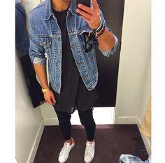 tênis branco, calça preta, blusa preta, jaqueta jeans azul e óculos preto