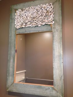 Handmade mirror seen in local restaurant with oyster shell decoration at top.