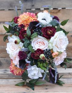 This bouquet is wildflower inspired bouquet made with marsala burgundy ranunculus, dahlias, lavender, roses, berries, ruscus and anemones,