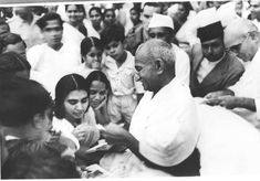 Mahatma Gandhi signing autographs, in return for donations to the Harijan Fund. This happy picture of Gandhi was taken at Juhu in Mumbai where he spent an occasional rest.