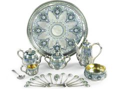 A silver and champlevé enamel tea and coffee service, Ovchinnikov, Moscow, 1879-1883. Comprising a teapot, coffee pot, covered sugar bowl, cream jug and waist bowl, a circular tray, twelve teaspoons with rope-twist handles, a sugar shovel, a pair of sugar tongs and a sugar sifter, decorated in opaque and translucent polychrome enamels with lambrequins of oval medallions within stylised foliage.