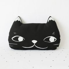 This pillow is made from canvas with a sweet and mischievous cat face painted on the front and the back. One face is black with a white painted face