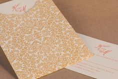 A letterpress printed invitation with a pop of watermelon ink is perfectly paired with an antique gold floral sleeve.