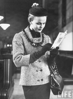 Model reading while posing in a train station while wearing new fashion, 1953. LIFE. Photographer: Gordon Parks.
