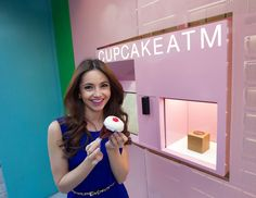 De cupcakes uit deze automaat zijn net zo zoet als de vrouw die erbij staat. Daar word je meteen vrolijk van!
