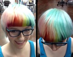 Platinum blonde hair in a short cut with blunt straight fringe. Color used in hair was Paul Mitchell Inkworks. Red, orange, yellow, green accent slices through the fringe. Fun hair color!