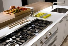 Kitchen island with row cooktop - also like the style of white and butcher block for the counter (bulthaup)
