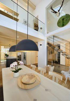 Die Lichtgalerie über dem Esszimmer ist das Schlüsselelement im Wohn- und Essbereich des Bau-Fritz Hauses Alpenchic. Die Galerie setzt den Holztisch in S