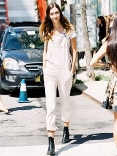 White overalls cuffed at the ankle is worn over a white tee and paired with black ankle boots.