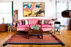 Vintage tufted pink sofa anchors room.