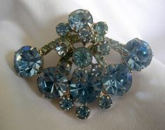 Beautiful prong set blue rhinestone brooch in a silver tone setting. Each stone is round and diamond cut with foil backing. Classic and elegant,