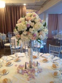 Wedding centerpiece of white hydrangea, white stock, white roses, Sahara roses, and lavender roses atop a mercury glass vase with chandelier crystals, surrounded by rose petals and votives.  Doristhefloristt@aol.com